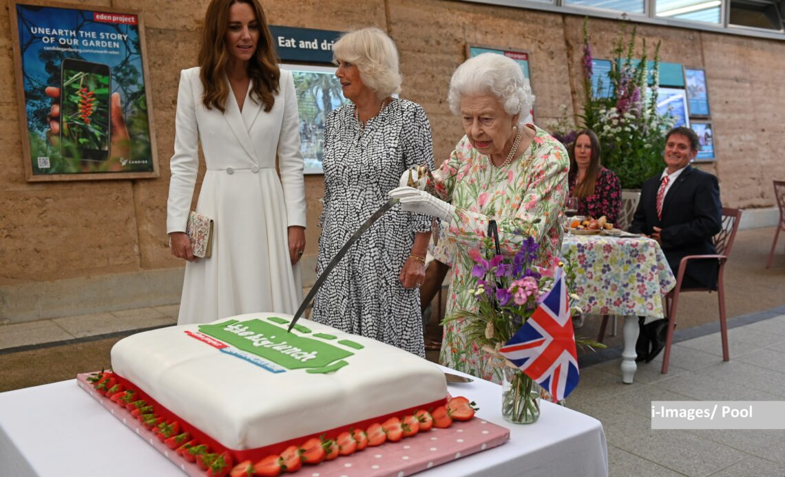 The Queen cuts cake with a sword